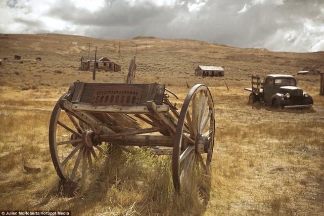 Деревянная тележка нафоне ржавого грузовика (более поздних времен) идвух сараев нагоризонте