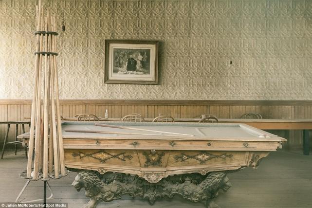 Бильярдный стол, покрытый пылью, ицелая дюжина бильярдных киев, которые оставили красиво стоять