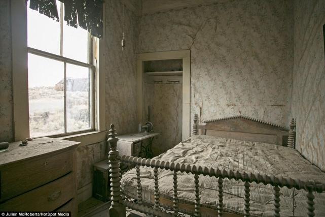 Чудом сохранившаяся спальня, вкоторой остался даже матрас накровати иобои настенах, атакже швейная машинка натумбочке
